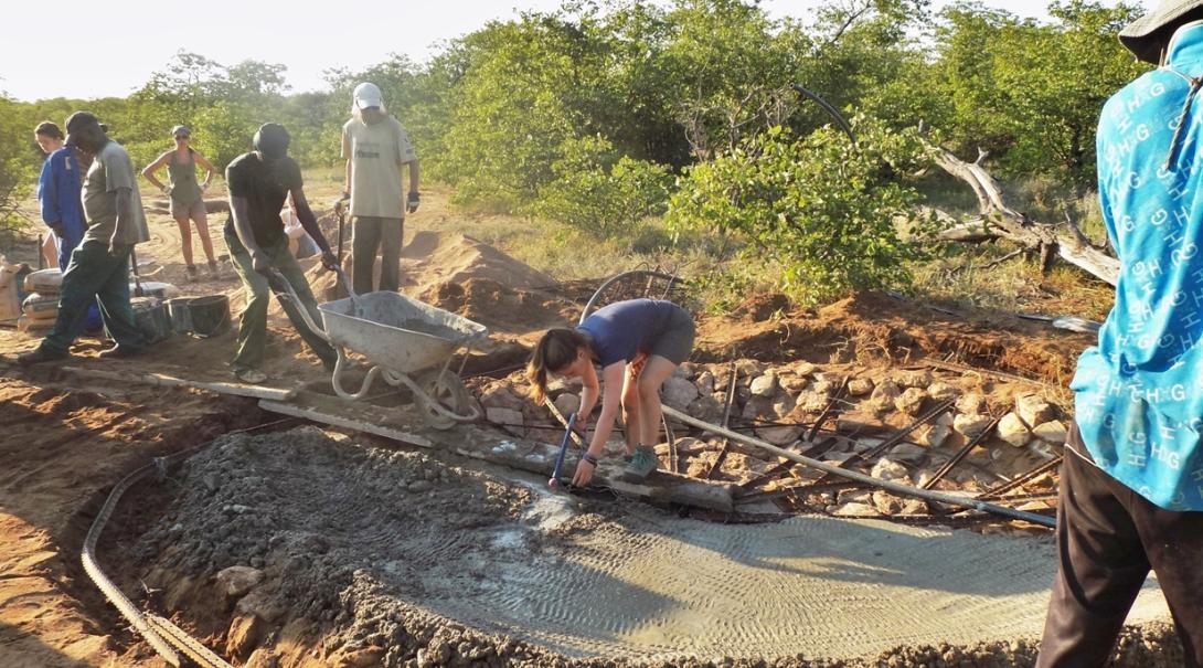 ボツワナで野生動物の水飲み場の建設にあたる高校生ボランティア